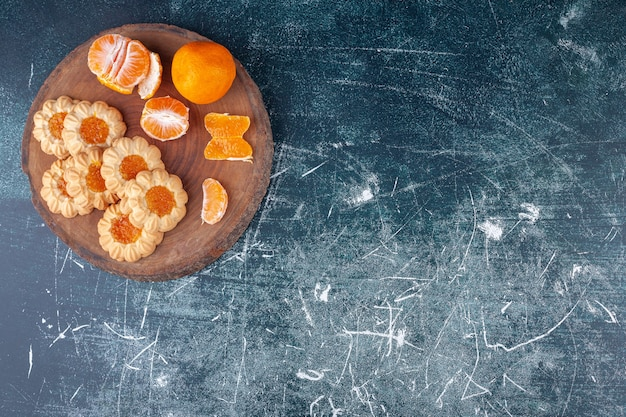 Holzstück mit clementinenfrüchten und geleeplätzchen auf marmorhintergrund.