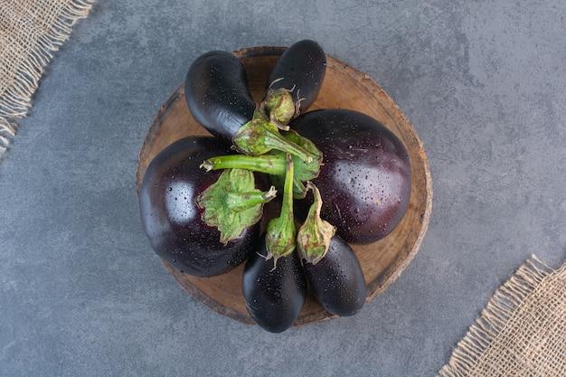 Holzstück von natürlichen frischen auberginen auf steinoberfläche
