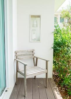 Holzstuhl auf bretterboden und weißem wandhohlraum