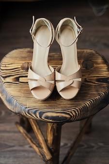 Holzstuhl darauf rosa hochhackige sandalen, leicht rosa