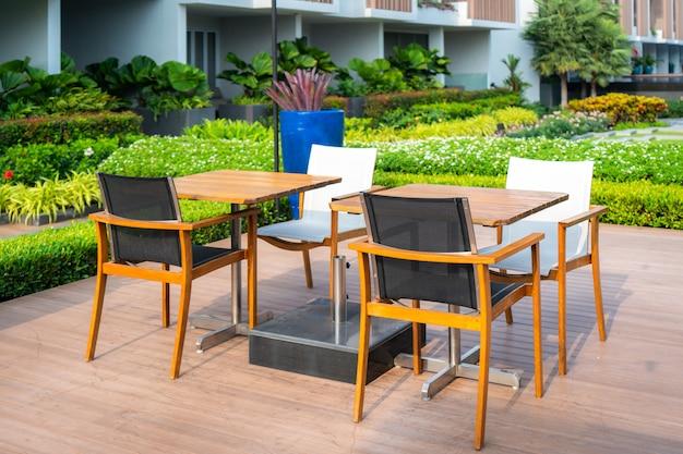 Holzstuhl im hölzernen patio am grünen garten im haus