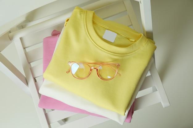 Holzstuhl mit gelben, rosa und weißen sweatshirts und brille