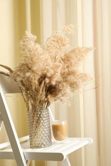 Holzstuhl mit vase mit feldblumen und glas latte