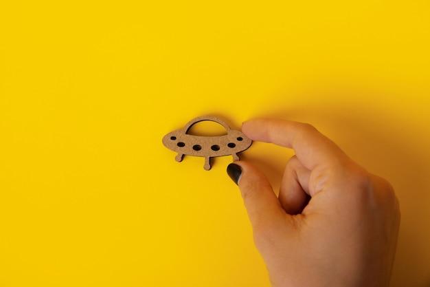 Holzsymbol-ufo in der hand über gelbem hintergrund