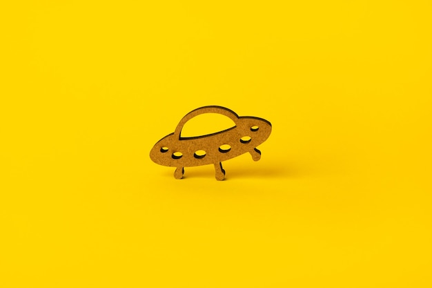Holzsymbol-ufo über gelbem hintergrund