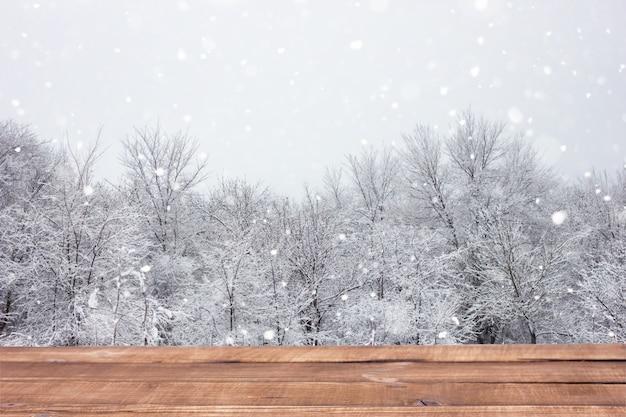 Holztabelle auf dem hintergrund des winterwaldes.