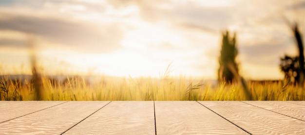 Holztabelle mit unscharfem hintergrund des weizenfeldes und des sonnenuntergangs für produktanzeige