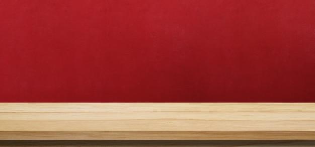Holztabelle und roter wandhintergrund für montagebanner der lebensmittel- und produktanzeige