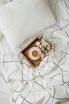 Holztablett kaffee und kerzen mit blumen auf dem bett. frühstück im bett. hygge-konzept.