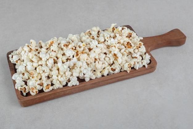 Holztablett mit einem griff, der mit einer portion popcorn auf marmortisch gefüllt ist.