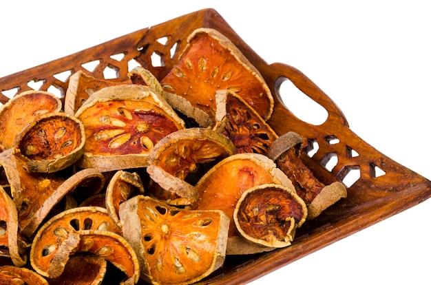 Holztablett mit getrockneten baelfrüchten isoliert auf weißer oberfläche