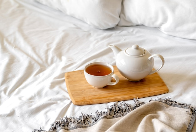 Holztablett mit tasse tee und teekanne
