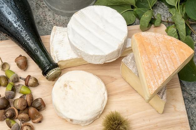 Holztablett mit verschiedenen französischen käsesorten und einer flasche apfelwein