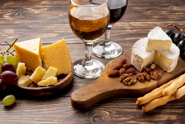 Holztablett mit verschiedenen käsesorten zur weinprobe