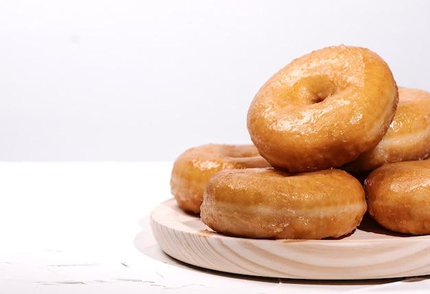 Holztablett mit vielen donuts auf einem weißen raum