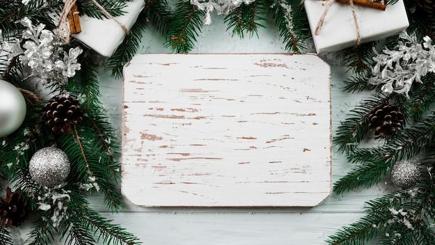 Holztablette zwischen weihnachtszweigen