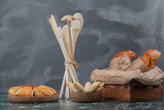 Holzteller der bäckerei mit küchenwerkzeugen auf marmorhintergrund.