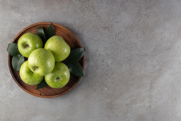 Holzteller der grünen äpfel auf steinhintergrund gelegt.