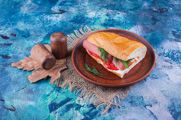 Holzteller des hausgemachten frischen sandwiches auf blauer oberfläche.