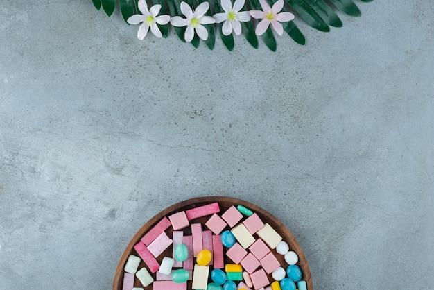 Holzteller mit buntem kaugummi auf steinoberfläche.