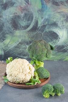 Holzteller mit frischem grünem brokkoli und blumenkohl auf steinoberfläche