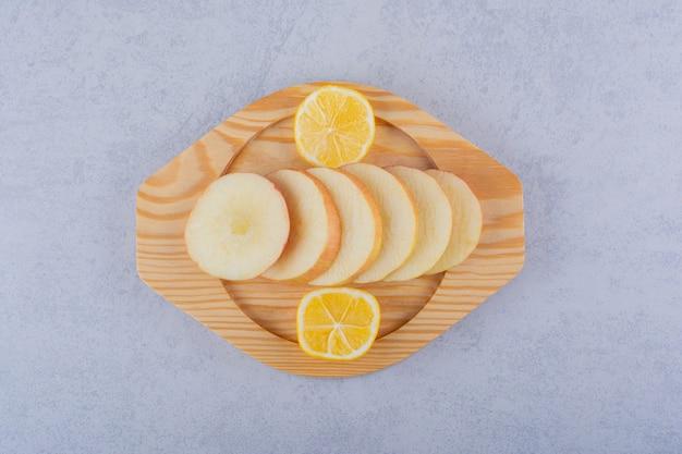 Holzteller mit frischen apfelscheiben und zitrone auf stein.