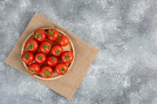 Holzteller mit frischen bio-tomaten auf marmor.