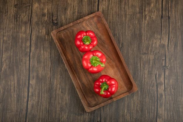 Holzteller mit frischen roten paprikaschoten auf holzoberfläche