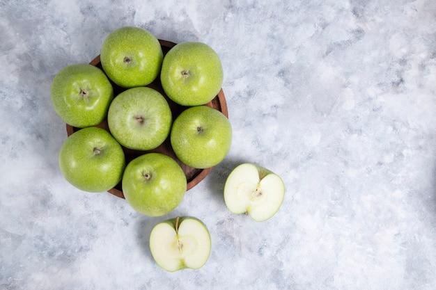 Holzteller mit ganzen und in scheiben geschnittenen frischen reifen grünen apfelfrüchten. hochwertiges foto
