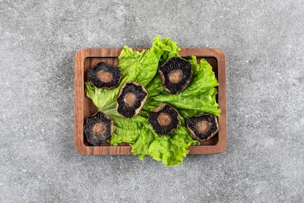 Holzteller mit gebratenen pilzen mit salat auf steintisch.