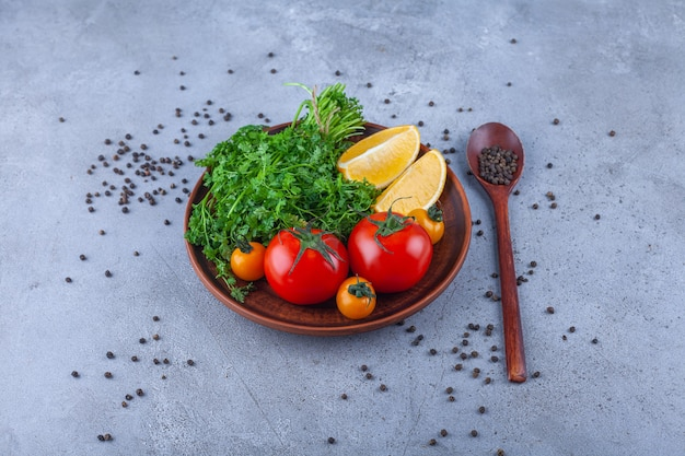 Holzteller mit gemüse, tomaten und zitrone auf steinoberfläche.