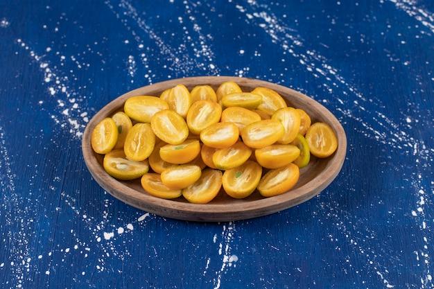 Holzteller mit geschnittenen kumquat-früchten auf marmoroberfläche.