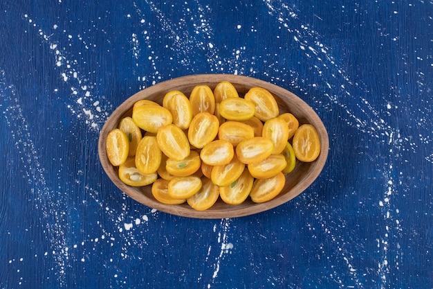 Holzteller mit geschnittenen kumquat-früchten auf marmoroberfläche