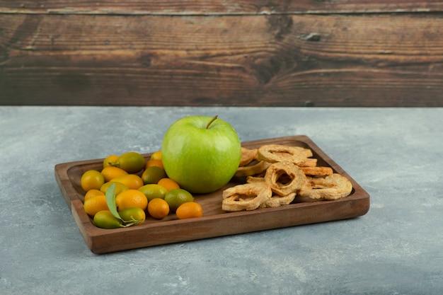 Holzteller mit getrockneten apfelringen, grünem apfel und cumquats auf marmoroberfläche.