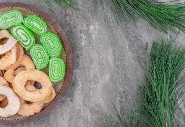 Holzteller mit getrockneten apfelringen und grünen marmeladenbonbons auf marmoroberfläche.