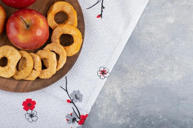 Holzteller mit getrockneten apfelringen und rotem apfel auf weißer tischdecke.