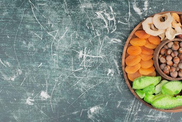 Holzteller mit getrockneten früchten auf marmorhintergrund