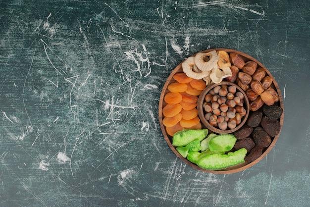 Holzteller mit getrockneten früchten auf marmorwand