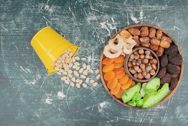 Holzteller mit getrockneten früchten und eimer nüsse.