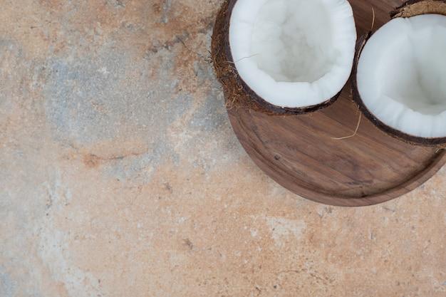 Holzteller mit halb geschnittenen reifen kokosnüssen auf marmoroberfläche.
