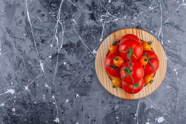 Holzteller mit kirschen und roten tomaten auf marmoroberfläche