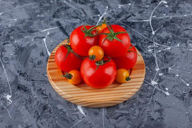 Holzteller mit kirschen und roten tomaten auf marmoroberfläche.