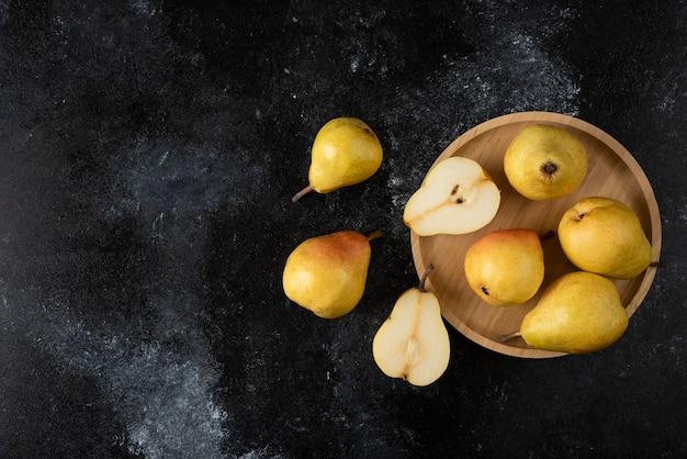 Holzteller mit leckeren gelben birnen auf schwarzer oberfläche.