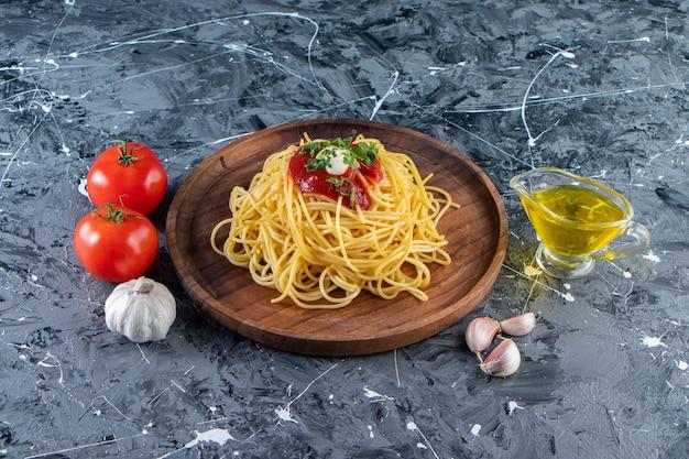 Holzteller mit leckeren spaghetti mit tomatensauce und gemüse auf marmoroberfläche.