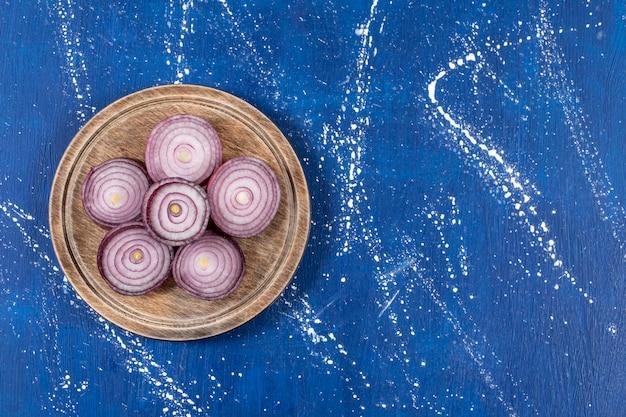 Holzteller mit lila zwiebelringen auf marmoroberfläche