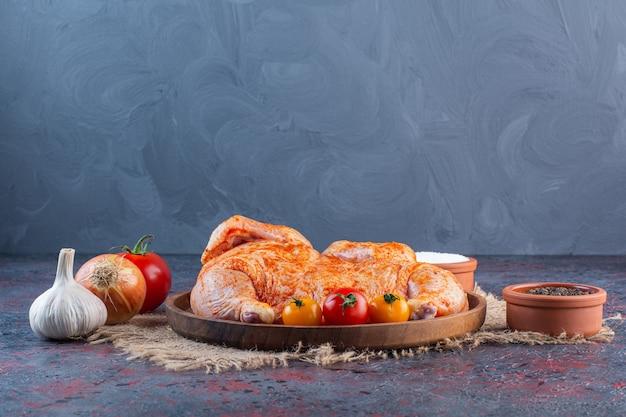 Holzteller mit mariniertem ganzen huhn auf marmoroberfläche