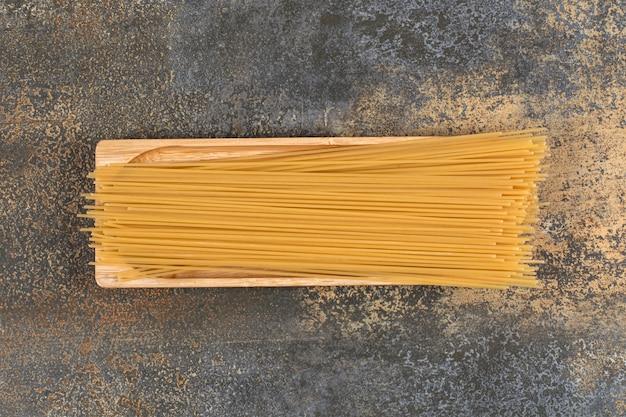 Holzteller mit rohen trockenen spaghetti auf marmoroberfläche.