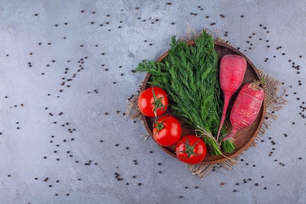 Holzteller mit rotem rettich, tomaten und dill auf steinhintergrund.