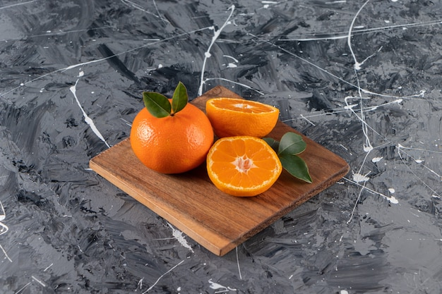 Holzteller mit saftigen ganzen und geschnittenen orangen auf marmortisch.