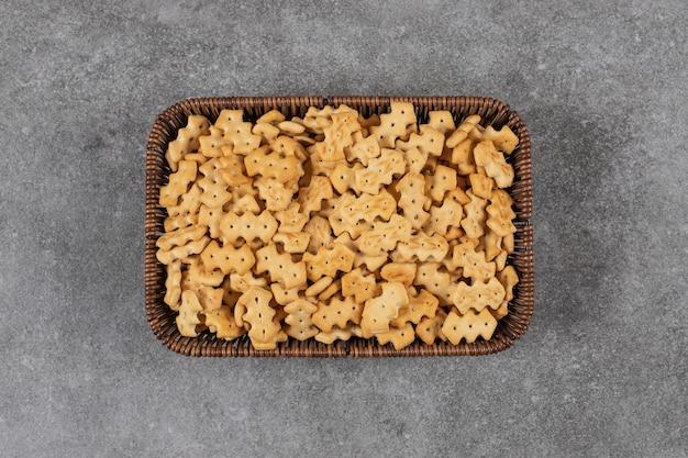 Holzteller mit salzigen crackern auf steintisch gelegt